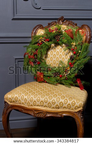 beautiful Christmas green festive wreath from the Christmas tree lying on a chair - stock photo