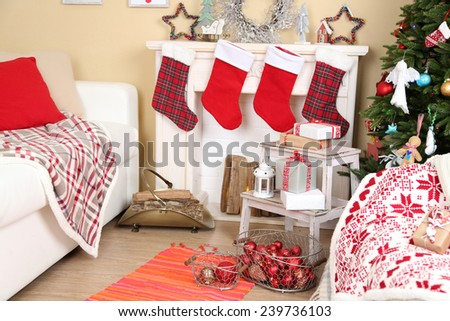 Beautiful Christmas interior with sofa, decorative fireplace and fir tree - stock photo