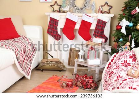 Beautiful Christmas interior with sofa, decorative fireplace and fir tree - stock photo