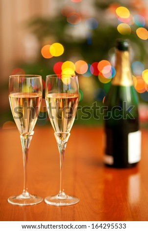 Beautiful Christmas setting with champagne and Christmas tree in the background - stock photo