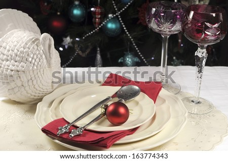 Beautiful Christmas table setting in front of Christmas Tree, with red crystal wine goblet glasses and turkey tureen. - stock photo