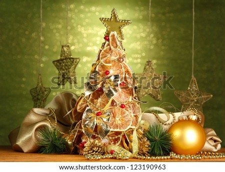 beautiful christmas tree of dry lemons with decor, on shine green background - stock photo