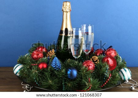 Beautiful Christmas wreath in composition with champagne on blue background - stock photo
