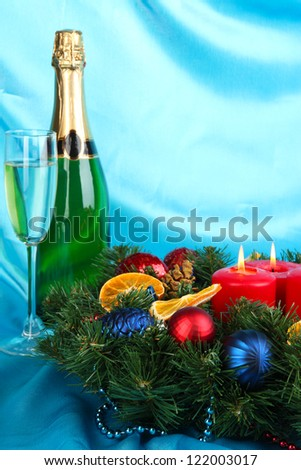 Beautiful Christmas wreath in composition with champagne on blue fabric background - stock photo