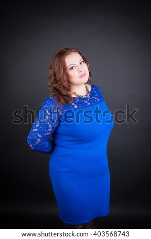 Beautiful chubby woman in a blue dress with lace large size. Gentle make-up on the smooth young skin lush model - stock photo
