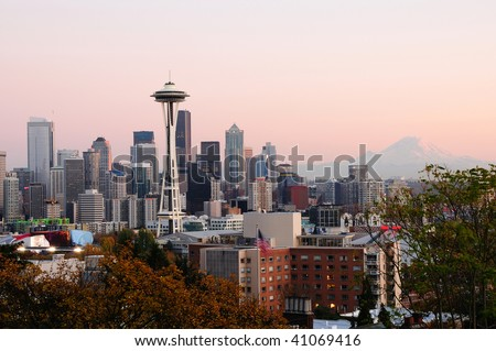 Beautiful city of Seattle glowing at dusk with Mount Rainier in the backdrop - stock photo