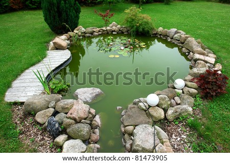 Beautiful classical design garden fish pond in a well cared backyard gardening background - stock photo