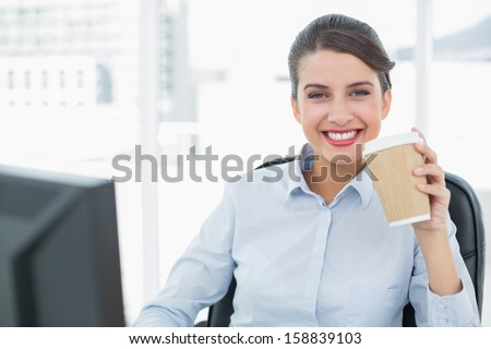Beautiful classy brown haired businesswoman enjoying coffee in bright office - stock photo