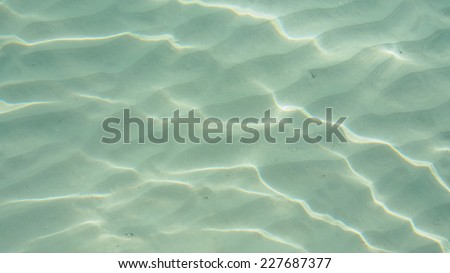 beautiful clear beach ripple water reflecting in the sun - stock photo