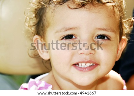 Beautiful close-up of brown eyes and fair skin and a great big smile showing her perfect baby teeth. - stock photo