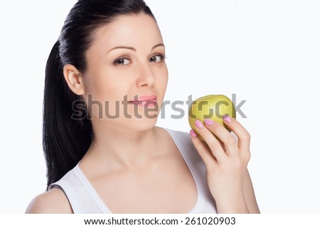 Beautiful close-up portrait of young woman with green apple. Healthy food concept. Skin care and beauty. Vitamins and minerals. - stock photo