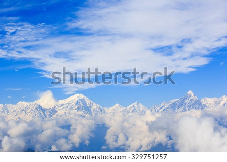 beautiful clouds and fog among  frozen mountain summits landscape - stock photo
