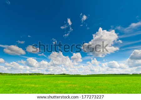 beautiful clouds cast shadows on the green field  - stock photo