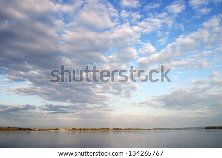 Beautiful clouds over the broad river - stock photo