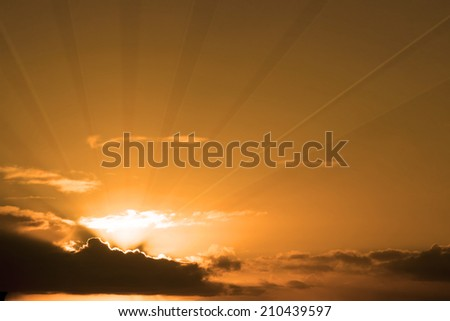 beautiful cloudy orange sunset sky in the wild Atlantic way, Ireland with sunbeams - stock photo