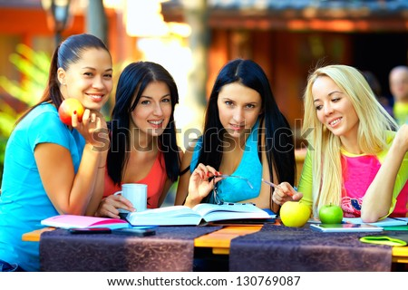 beautiful college girls studying outdoors - stock photo