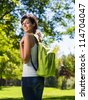 Beautiful college student with backpack  in park. Hispanic caucasian beautiful young woman on green background. - stock photo