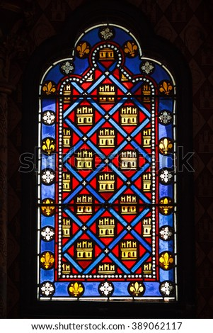 Beautiful colored ancient stained glass with a pattern of diamonds and castles - stock photo