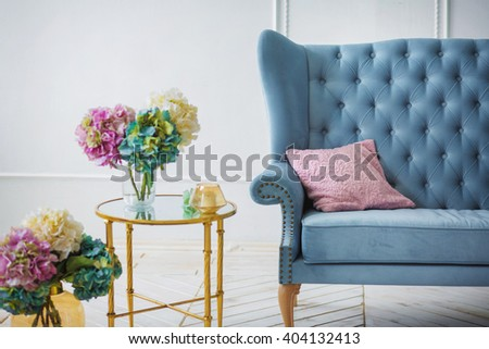 Beautiful colorful bouquet of hydrangeas is in a vase on a table with candles near the sofa with a pillow interior decor idea - stock photo
