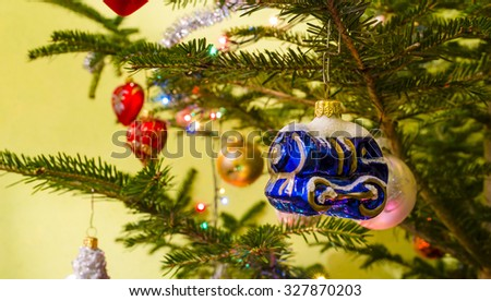 Beautiful colorful christmas decorations hanging on christmas tree with shiny glare - stock photo