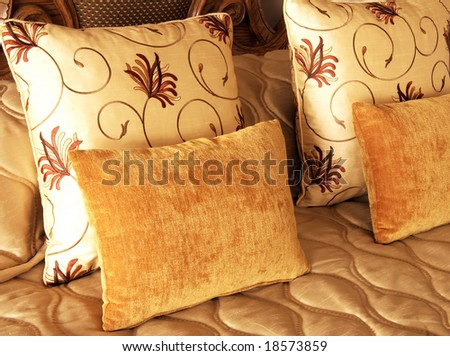 Beautiful colorful cushions on bed in guest lodge - stock photo