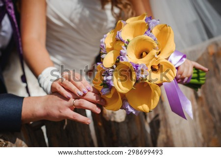beautiful colorful fresh flowers wedding bouquet in bride's arms - stock photo