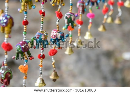 Beautiful colorful handmade wind chimes with bells and small decorated toy elephant model hanging in a local store in Rajasthan India. Decorative hangings. - stock photo