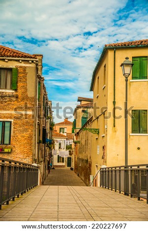 Beautiful colorful image of a street (Calle Larga Rosa) in Venice with a bridge, old houses, lanterns, and cloudy sky above. - stock photo