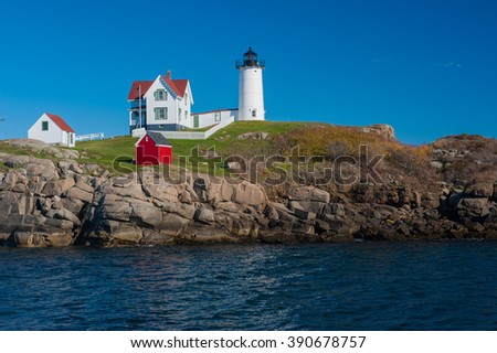 Beautiful colorful Lighthouse along Atlantic Ocean coast in New England marking lighting rocky shore - stock photo