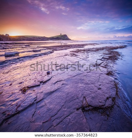 Beautiful colorful sunrise with rocks and low tide at Kimmeridge Bay, Dorset, UK - stock photo