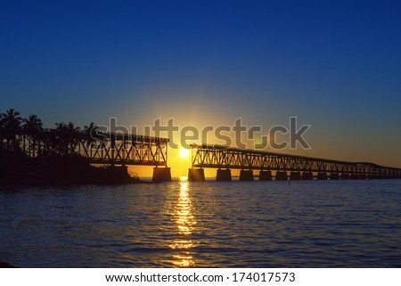 Beautiful colorful sunset or sunrise with broken bridge - stock photo