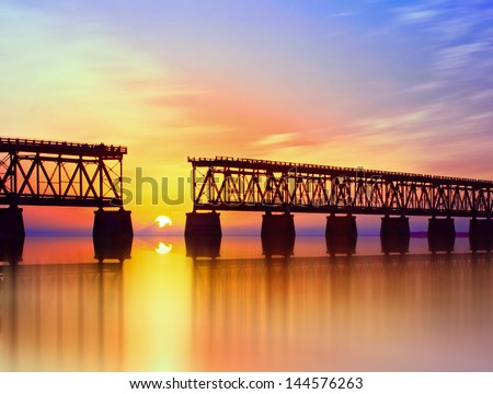 Beautiful colorful sunset or sunrise with broken bridge and cloudy sky. Taken at Bahia Honda state park in the Florida Keys, near famous tourist destination of Key West. - stock photo
