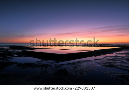 Beautiful colours in the sky about hour before sunrise at Wambarra, NSW, Australia and vivid reflections in the rock pool. - stock photo