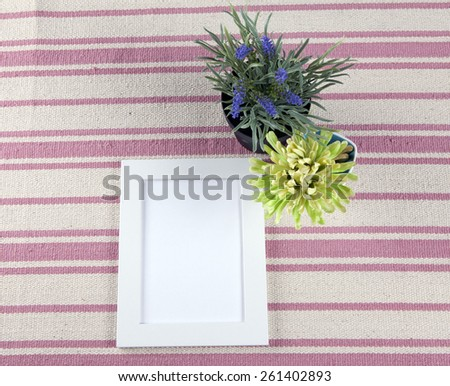 Beautiful composition with photo frames and flowers on a background of rustic rug. - stock photo