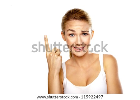 Beautiful confused woman with a raised eyebrow and quizzical expression pointing with her finger above her head isolated on white - stock photo