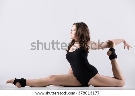 Beautiful cool young fit gymnast athlete woman in black leotard working out, dancing, doing art gymnastics, sitting in splits, full length, studio, white background, isolated - stock photo