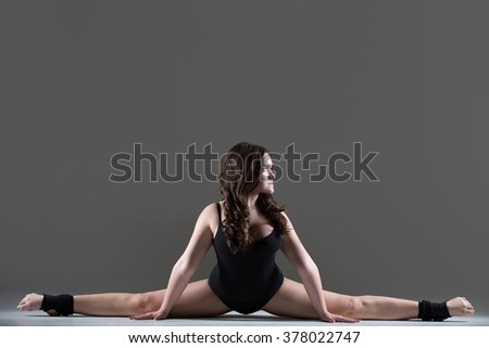 Beautiful cool young fit gymnast athlete woman in black leotard working out, dancing, doing art gymnastics, performing a side split, full length, studio, gray background - stock photo