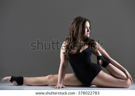 Beautiful cool young fit gymnast athlete woman in black leotard working out, dancing, doing art gymnastics, sitting in splits, full length, studio, gray background - stock photo