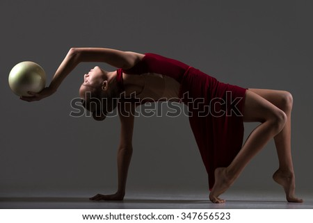 Beautiful cool young fit gymnast athlete woman in sportswear red dress working out, doing art gymnastics bridge exercise with white ball, dancing, full length, studio, dark background - stock photo