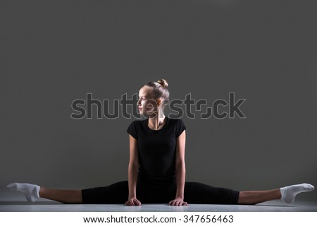 Beautiful cool young fit woman in sportswear doing art gymnastics, sitting in splits, straddle position, full length, studio image, dark background - stock photo