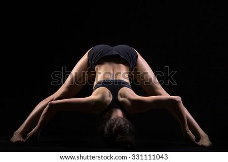 Beautiful cool young fit woman in sportswear doing sport exercise for flexibility, Wide Legged Forward Bend posture, Prasarita Padottanasana, studio, black background - stock photo