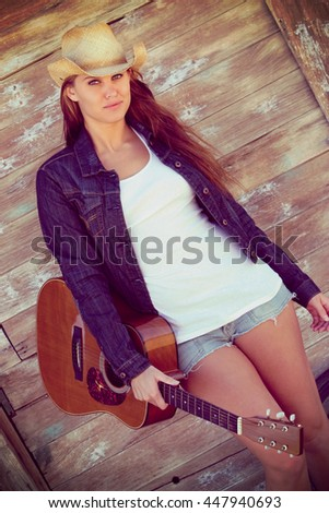 Beautiful country girl holding guitar - stock photo
