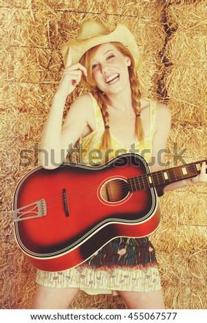 Beautiful country girl playing guitar - stock photo