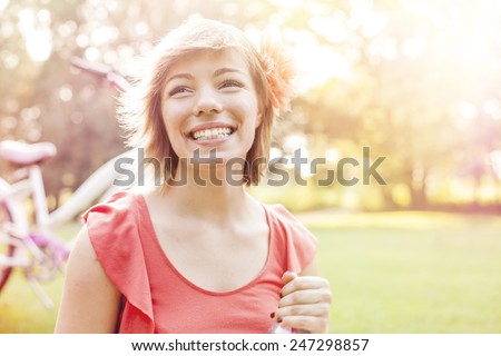Beautiful country girl riding a bike through nature, enjoying sunny day.  - stock photo