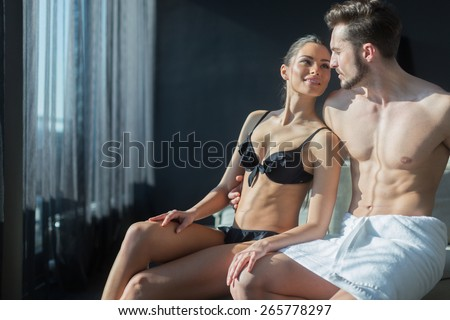 Beautiful couple being in love on their honeymoon in a luxurious hotel room while being half naked - stock photo