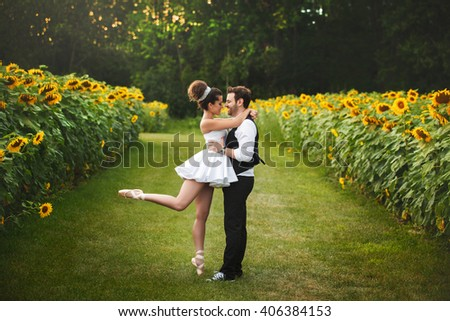 beautiful couple bride and groom hugging and dancing on the sunflower field - stock photo
