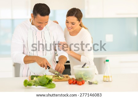 beautiful couple cooking together in home kitchen - stock photo