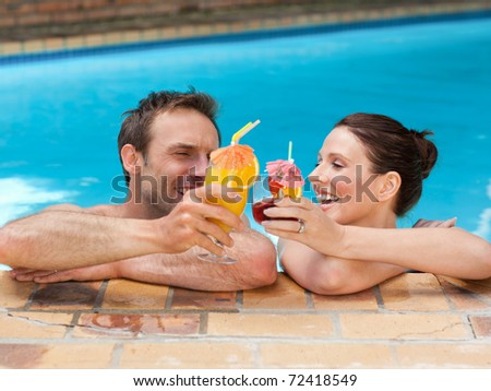 Beautiful couple drinking cocktails in the swimming pool - stock photo