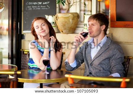 Beautiful couple enjoying their glasses of red wine in a cafe - stock photo
