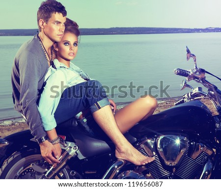 Beautiful couple family sitting on lake shore on motor bike - stock photo